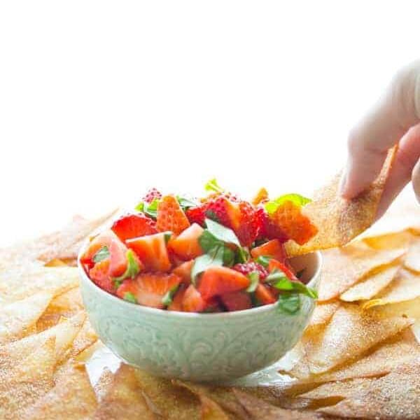 hand dipping a wonton chip into strawberry bruschetta