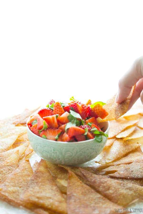Strawberry Bruschetta in a blue bowl with someone dipping a Wonton Chip into it