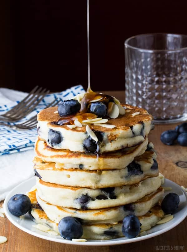 Stack of Almond Blueberry Pancakes on plate with syrup drizzling on top