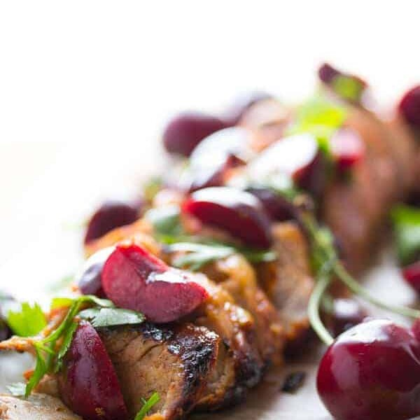 close up of chipotle grilled pork tenderloin with fresh cherry salsa on parchment