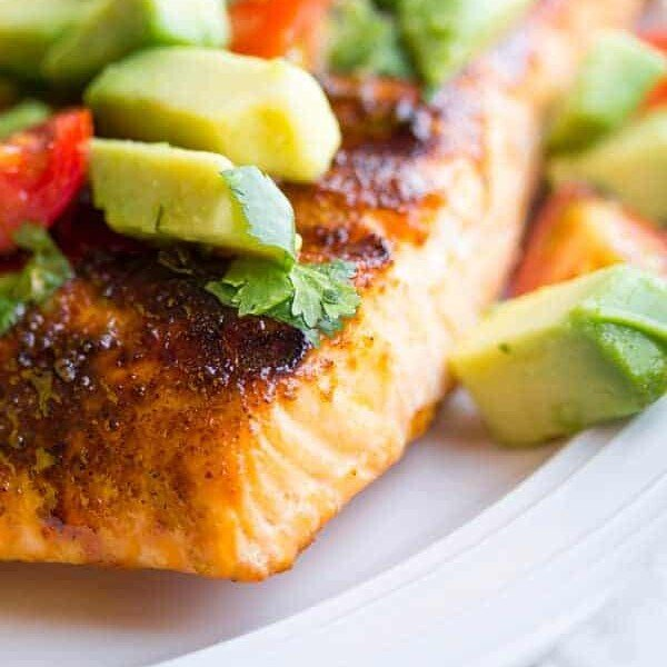 Close up of chili-rubbed salmon on a white plate topped with avocado salsa