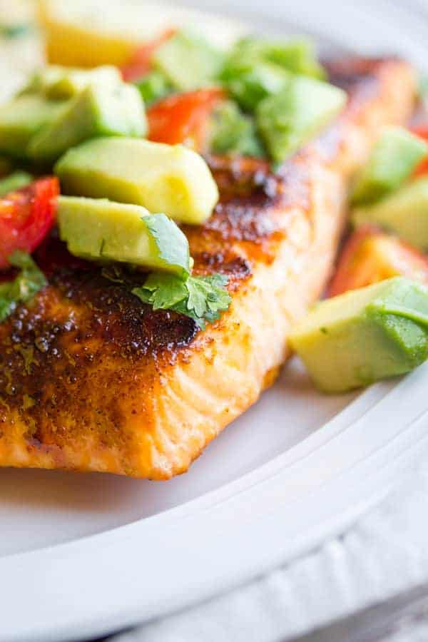 close up shot of chili rubbed salmon with avocado salsa on top