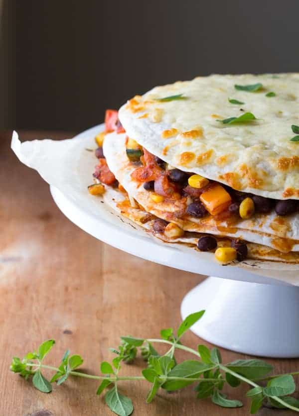 Garden Vegetable Black Bean Tortilla Stack on serving platter with a sprig of oregano