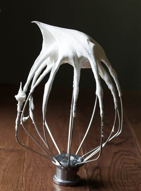 Stainless steel wire whip sitting upside down with meringue stuck to it