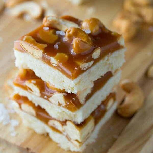 stack of three salted caramel bars with cashews on wood board