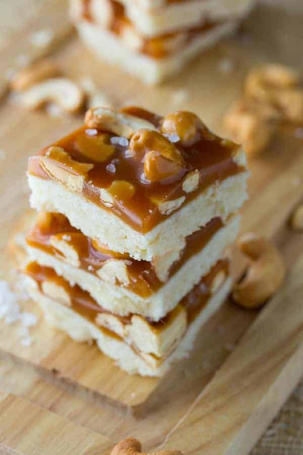 Stack of three Cashew Salted Caramel Bars on cutting board