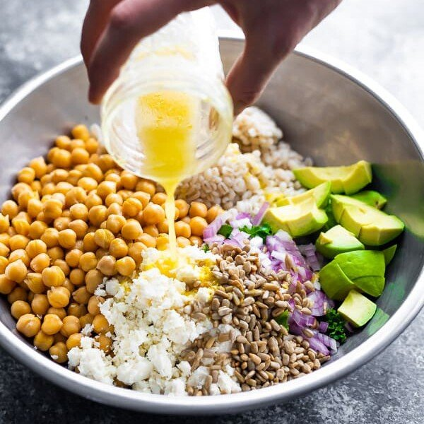 a hand pouring honey lemon vinaigrette onto a kale barley salad with feta and avocado