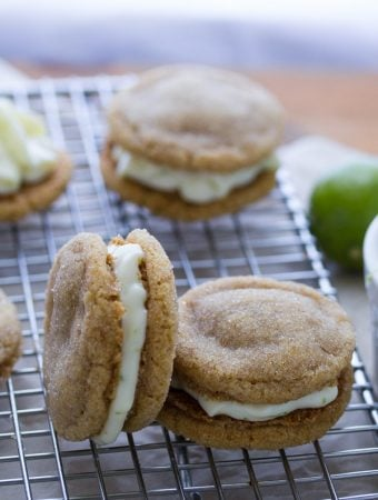 five key lime pie sandwich cookies on wire rack with lime in background