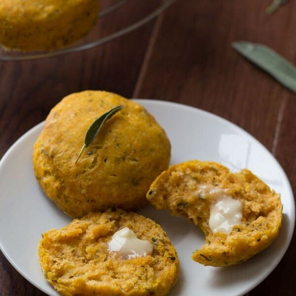 pumpkin biscuits with sage on white plate with butter
