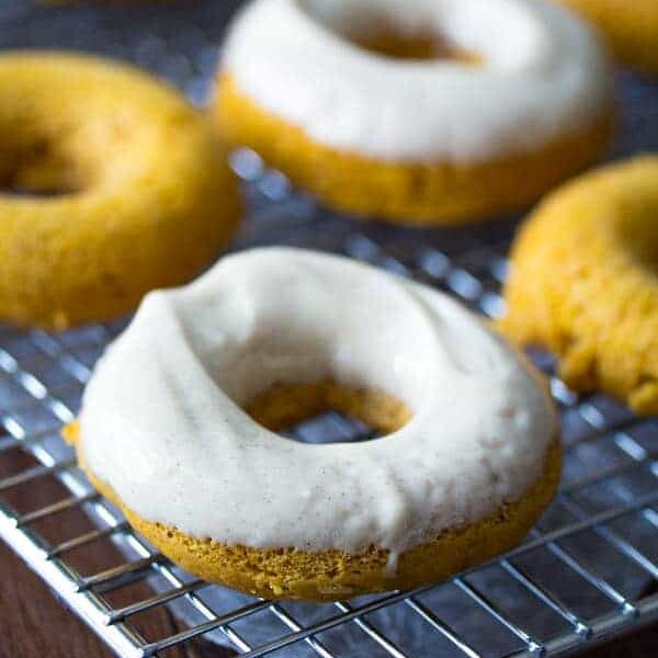 four baked pumpkin donuts with cream cheese on wire rack