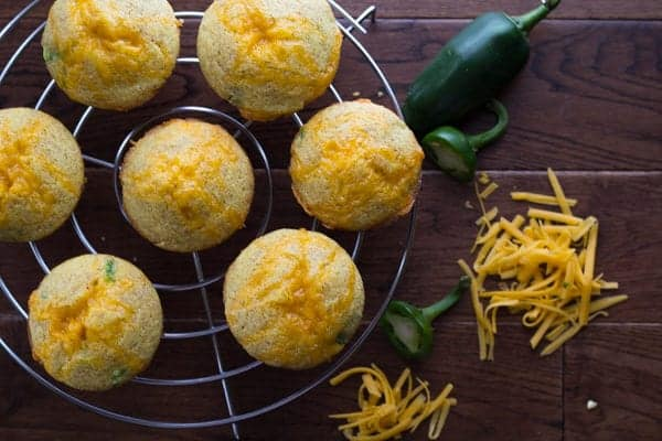 overhead shot of seven Jalapeño Popper Cornbread Muffins on wire rack with grated cheese on side