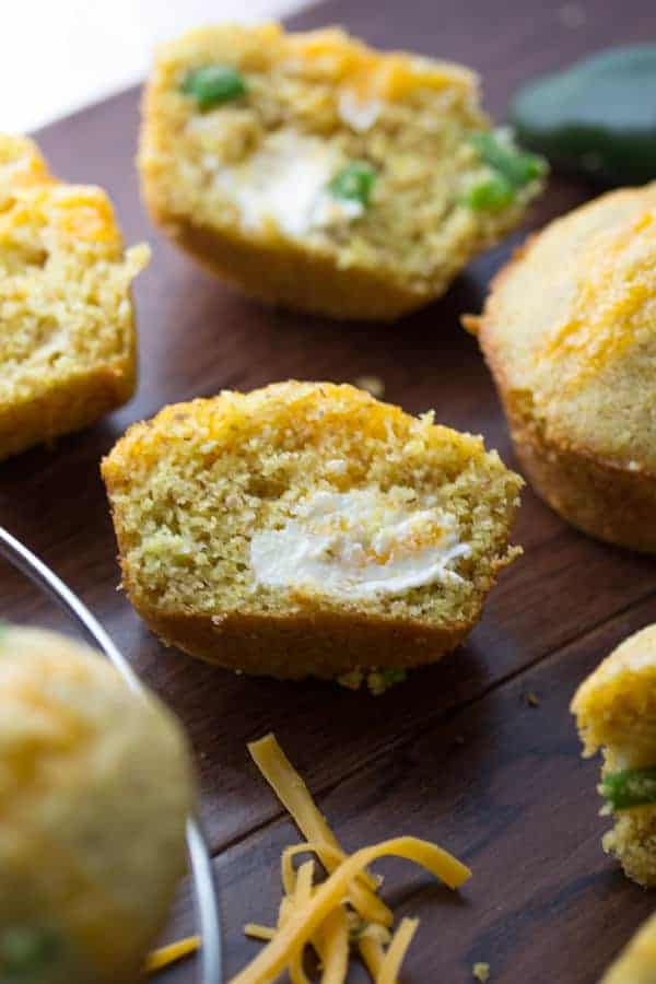 Jalapeño Popper Cornbread Muffins on wood tray sliced with butter