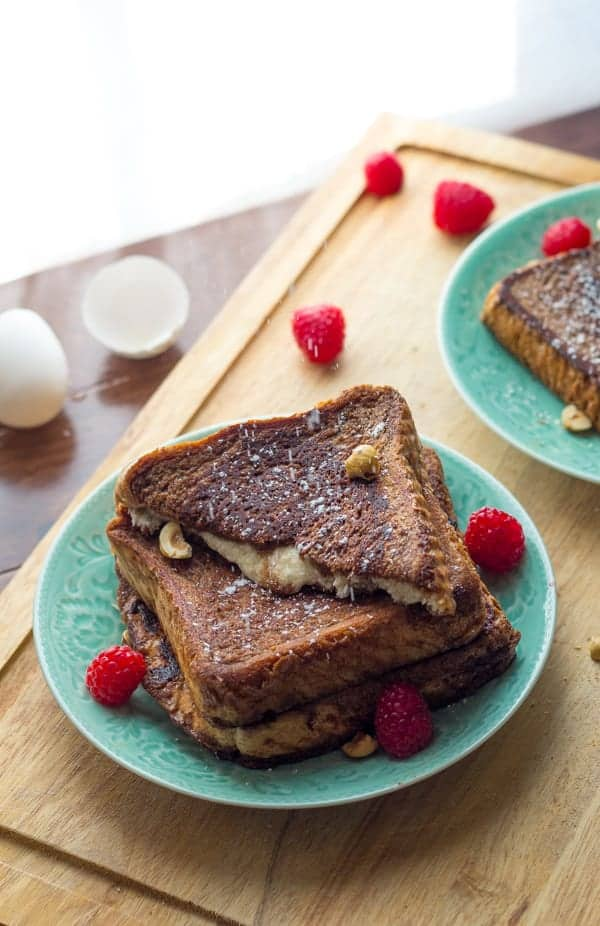 Mascarpone Stuffed French Toast stacked on plate with icing sugar falling over it