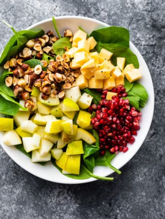 overhead shot of spinach pear salad with gouda and hazelnuts in a large white bowl