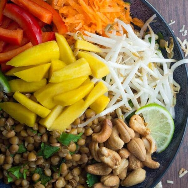 mango cashew lentil salad with coconut lime dressing in navy blue bowl