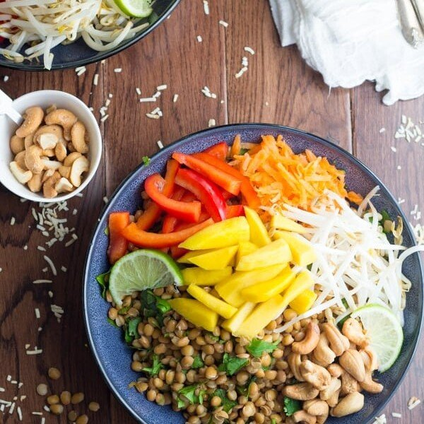 tropical lentil bowl with coconut lime dressing in navy blue bowl on wood table