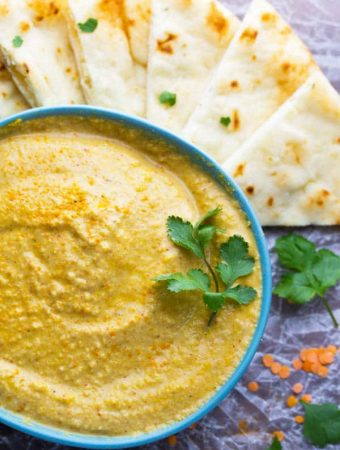 close up of masala spiced lentil hummus with sliced pitas