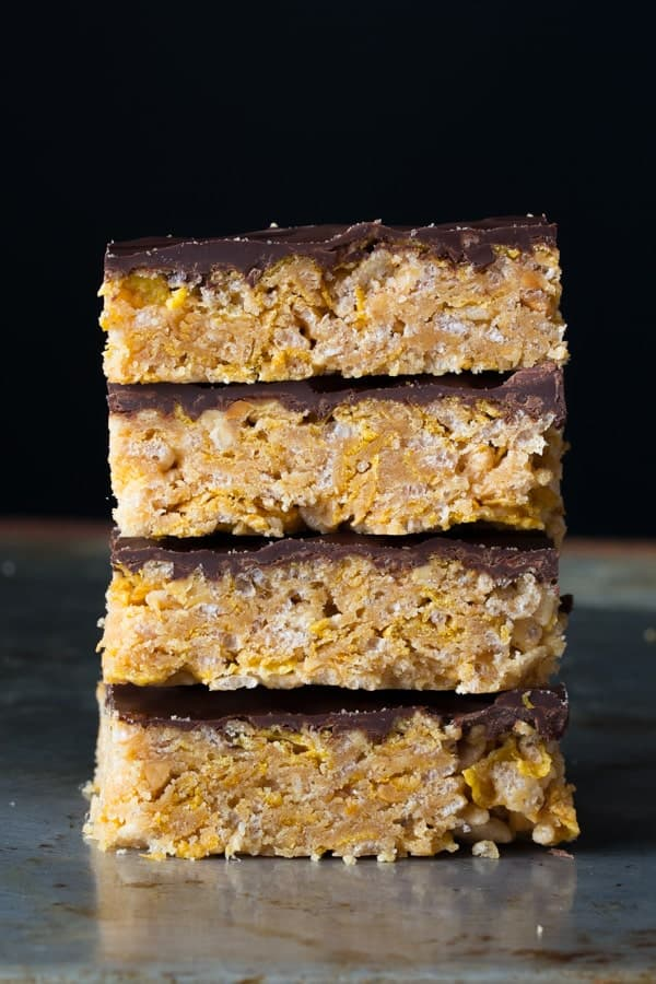 a stack of four no bake peanut butter bars showing the layers