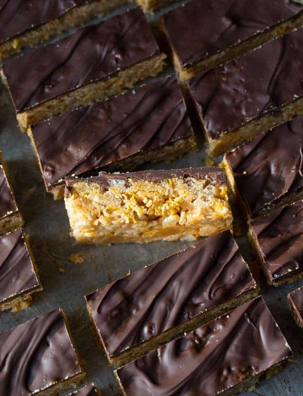 rows of no bake peanut butter bars showing chocolate tops with one on its side showing peanut butter base
