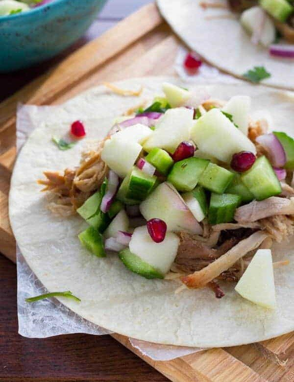 close up of of apple cider carnitas with fresh apple salsa on tortillas