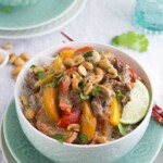 thai curry beef in white bowl with lime slice