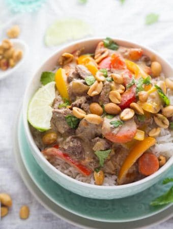thai curry beef in white bowl with lime slice and peanuts