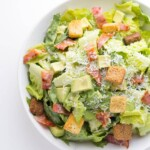 overhead shot of avocado caesar salad in white bowl