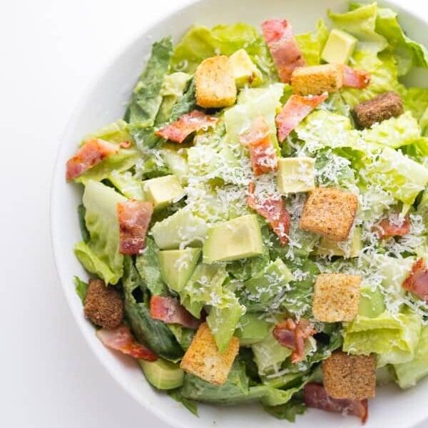overhead shot of avocado caesar salad in white bowl