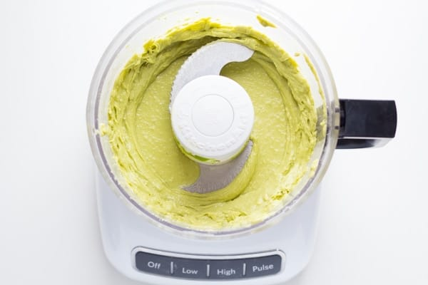 overhead view of food processor containing avocado caesar salad dressing after blending
