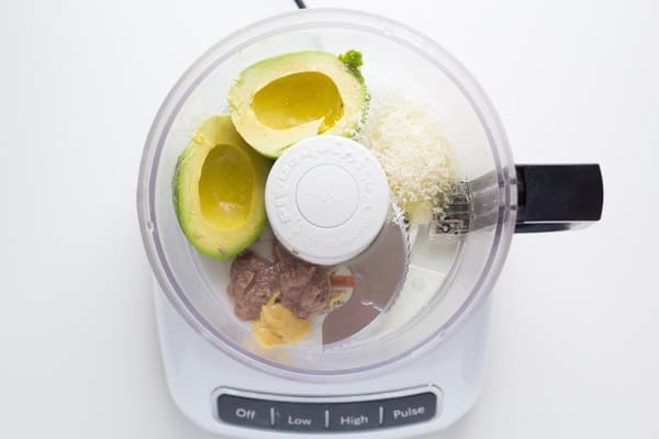 overhead view of food processor with avocado caesar salad dressing ingredients