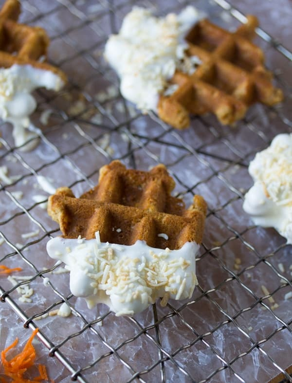 side angle view of carrot cake waffle bites dunked in cream cheese frosting and sitting on wire rack