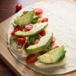 chicken and avocado caprese quesadillas on wood board