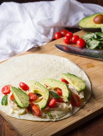chicken and avocado caprese quesadillas on wood board with knife in background