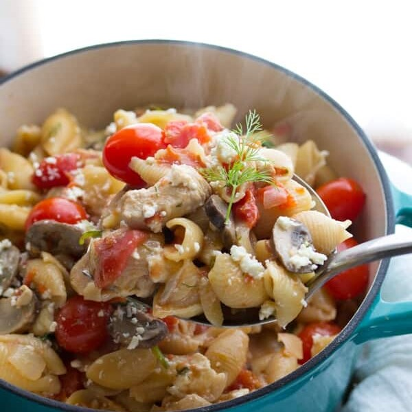 pasta with chicken feta and dill in large blue pot with spoon