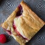 overhead shot of brown butter raspberry swirl cheesecake blondie on gray background