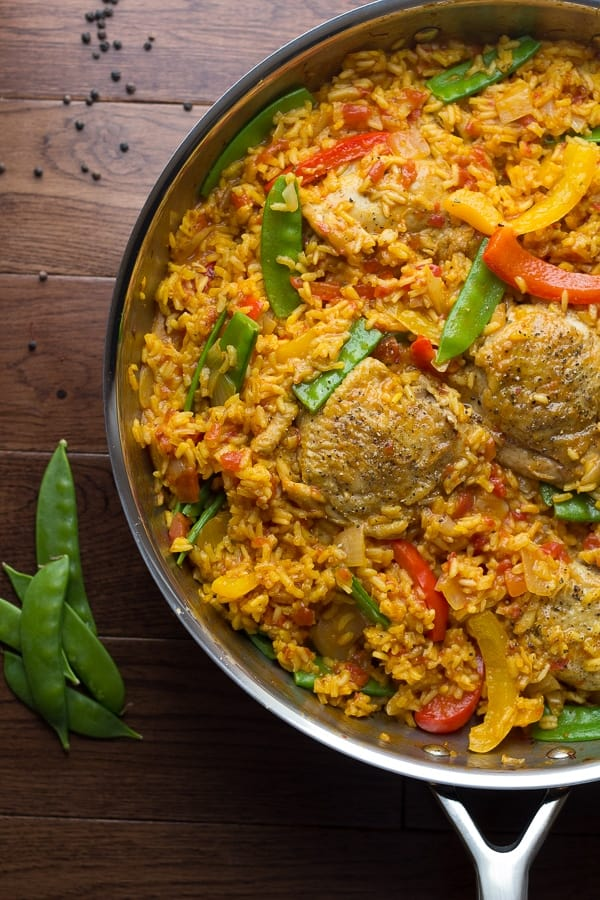 Spanish Chicken and Rice Skillet in a large pan with fresh snap peas on the side