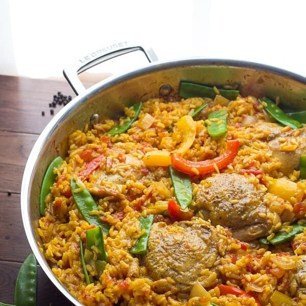 saffron chicken with peppers and peas in large pan