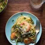 shrimp linguine with spring vegetables on blue plate with fork
