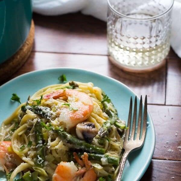shrimp linguine with spring vegetables on blue plate with fork