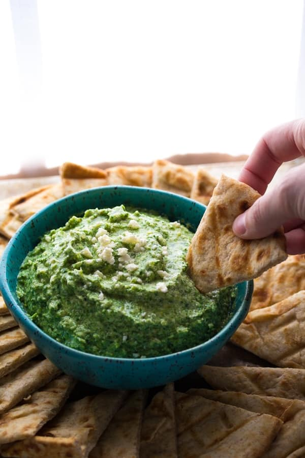 dipping a pita chip into a bowl of spinach artichoke whipped feta
