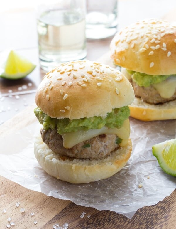 two tequila turkey sliders with guacamole on parchment with limes
