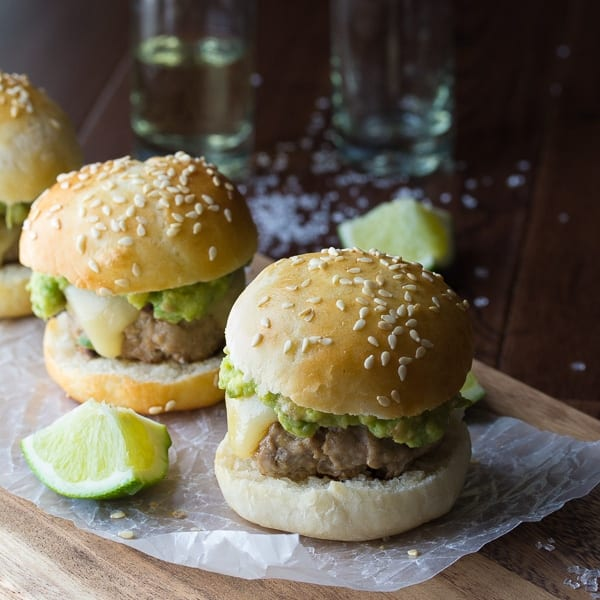 two tequila turkey sliders on cutting board with shots of tequila in the background