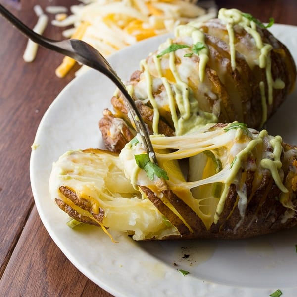 fork prying apart the layers of a hasselback potato revealing melted cheese and jalapenos