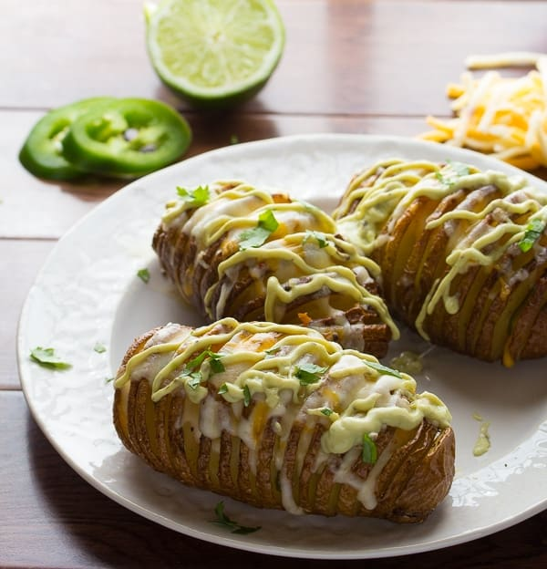 three jalapeno hasselback potatoes on a plate drizzled with avocado cream sauce