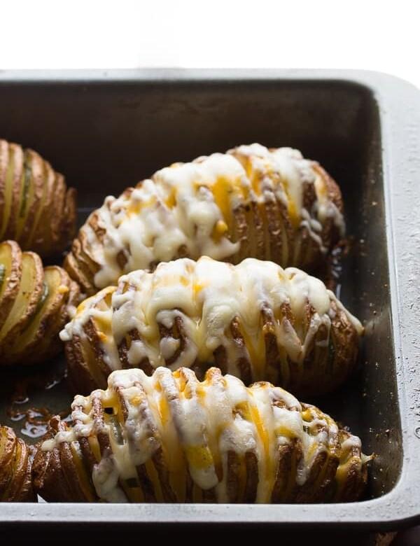 cheesy jalapeno hasselback potatoes with avocado cream sauce in pan