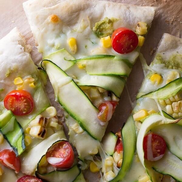 three slices of guacamole pizza with corn and zucchini