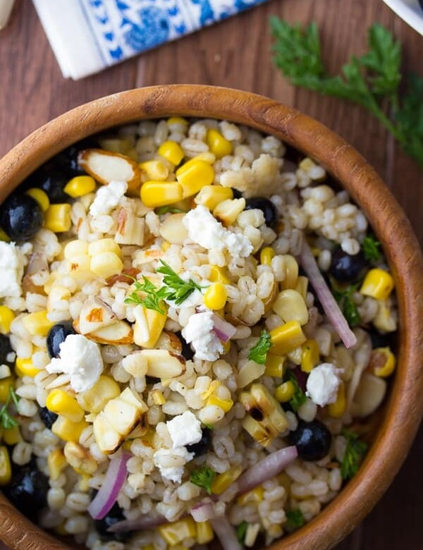 overhead view of Summer barley salad with corn and blueberries in wooden bowl