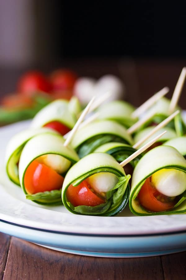 Rows of zucchini roll ups on ap late with tomatoes, basil, and mozzarella