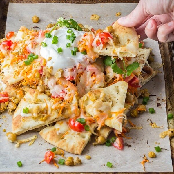 A hand picking up a spiced chickpea naan nacho from pile of nachos