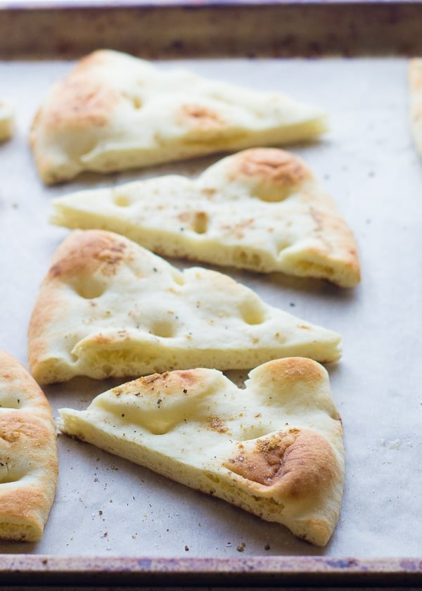 naan bread cut into wedges and arranged on a baking sheet